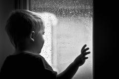 Garçon observant la pluie Photographie stock libre de droits
