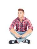 Garçon occasionnel songeur s'asseyant sur le plancher Photographie stock libre de droits