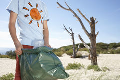 Garçon portant le sachet en plastique rempli de déchets sur la plage Image libre de droits