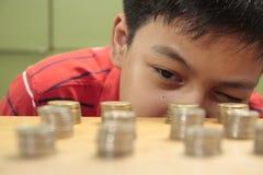 Garçon regardant des piles de pièces de monnaie Photographie stock