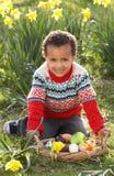 Garçon sur la chasse à oeuf de pâques dans le domaine de jonquille Photo libre de droits
