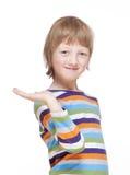 Garçon étirant son bras avec la paume, regard, souriant Photo stock
