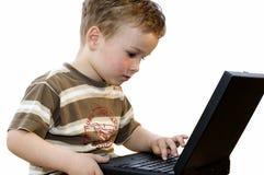 Garçon travaillant sur un ordinateur portatif Photographie stock libre de droits