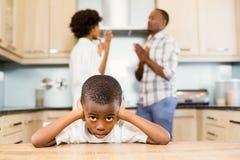 Garçon triste contre l'argumentation de parents Photo libre de droits