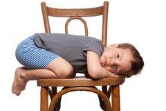Garçon triste s'asseyant sur la présidence Photographie stock libre de droits