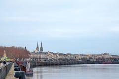 Garonne kajQuais de la Garonne på skymning med förbigå för folkmassa Den helgonAndre domkyrkan kan ses i bakgrund royaltyfria bilder