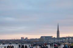 Garonne kajQuais de la Garonne på skymning med förbigå för folkmassa Saint Michelbasilikan kan ses i bakgrund royaltyfria bilder