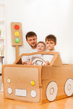Garçons conduisant le papa dans la voiture de jouet faite de boîte en carton Photo libre de droits