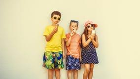 Garçons d'enfants et petite fille mangeant la crème glacée  Photographie stock