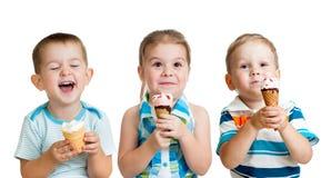 Garçons heureux et fille d'enfants mangeant la crême glacée d'isolement Photographie stock