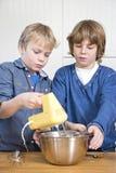 Garçons mélangeant la pâte dans une cuvette Images libres de droits