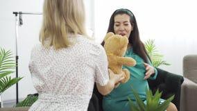 Garota com um vestido leve e pontilhado dando a sua amiga um presente para seu filho ainda não nascido Mulher-espera-morena em az video estoque