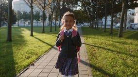 Garota de uniforme escolar está andando no parque com clima ensolarado, Steadicam filme