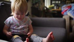 A garotinha olha para o smartphone e ri vídeos de arquivo
