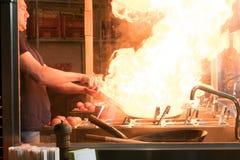 Garprozess in einem asiatischen Restaurant Koch ist Fischrogengemüse mit Gewürzen und Soße in einem Wok auf einer Flamme Lizenzfreie Stockbilder