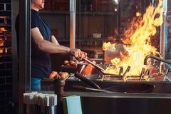 Garprozess in einem asiatischen Restaurant Koch ist Fischrogengemüse mit Gewürzen und Soße in einem Wok auf einer Flamme Stockbild