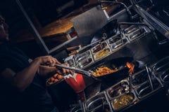 Garprozess in einem asiatischen Restaurant Koch rührt Gemüse im Wok Lizenzfreie Stockfotografie