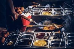 Garprozess in einem asiatischen Restaurant Koch rührt Gemüse im Wok Stockfotografie