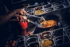 Garprozess in einem asiatischen Restaurant Koch rührt Gemüse im Wok Stockfoto