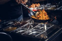 Garprozess in einem asiatischen Restaurant Koch rührt Gemüse im Wok Stockfotos