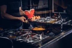 Garprozess in einem asiatischen Restaurant Koch rührt Gemüse im Wok Stockbilder