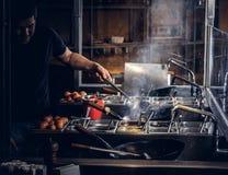 Garprozess in einem asiatischen Restaurant Koch rührt Gemüse im Wok Lizenzfreies Stockfoto