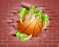 Garra con la bola de la cesta que se rompe a través de la pared de ladrillo Foto de archivo libre de regalías