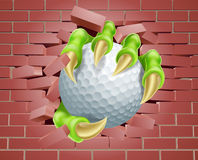 Garra con la pelota de golf que se rompe a través de la pared de ladrillo Fotografía de archivo libre de regalías