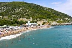 Garraf Beach in Sitges, Spain. SITGES, SPAIN - JULY 9, 2017: People enjoying, relaxing, sunbathing or bathing at the Garraf Beach in Sitges, a popular beach in Royalty Free Stock Photography