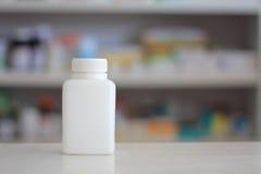 Garrafa branca da medicina com as prateleiras do borrão da droga no pha Foto de Stock Royalty Free