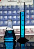 Garrafa cônica de laboratório de química e cilindro de medição em refletir o fundo da tabela de superfície e periódica imagens de stock
