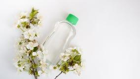 Garrafa colocada para a zombaria acima no fundo e nas flores brancos O conceito de produtos de beleza naturais imagem de stock