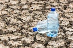 Garrafa com água na terra secada Foto de Stock