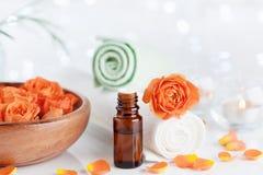 Garrafa com óleo essencial das flores cor-de-rosa na tabela branca Termas, aromaterapia, bem-estar, fundo da beleza Foto de Stock