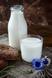 Garrafa com leite e vidro do leite na tabela de madeira Imagem de Stock