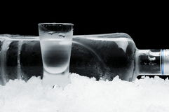 Garrafa com o vidro da vodca que encontra-se no gelo no fundo preto Imagens de Stock Royalty Free