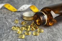 Garrafa com os comprimidos do óleo de fígado de bacalhau e a fita de medição foto de stock
