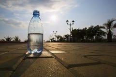 A garrafa da água custa no contexto da margem Fotografia de Stock Royalty Free