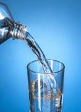 Garrafa da água que derrama em um vidro Imagens de Stock Royalty Free