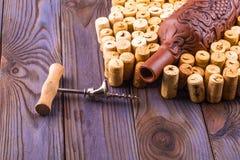 Garrafa da argila, corkscrew do metal e cortiça em uma tabela de madeira Foto de Stock Royalty Free