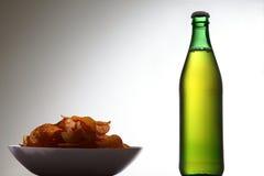 Garrafa da bebida ao lado das microplaquetas Foto de Stock Royalty Free