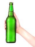 Garrafa da cerveja com a mão do homem que faz o brinde isolado no branco Fotos de Stock Royalty Free