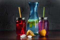 A garrafa da limonada com limões, gelo no vintage planked a tabela de madeira - ainda vida Imagem de Stock