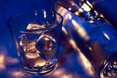 A garrafa da vodca na neve com vidro encheu-se com os cubos de gelo Foto de Stock