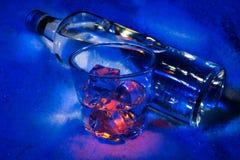 A garrafa da vodca na neve com vidro encheu-se com os cubos de gelo Imagens de Stock