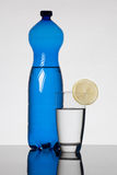 Garrafa de água azul e vidro enchidos com água Imagens de Stock