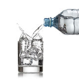 A garrafa de água fria derrama a água ao vidro no branco Imagens de Stock