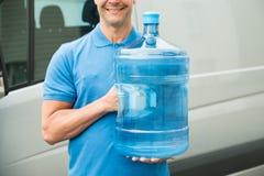 Garrafa de água levando do homem de entrega fotografia de stock royalty free