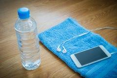 Garrafa de água plástica, fones de ouvido, telefone esperto e toalha no wo fotografia de stock