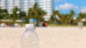 Garrafa de água plástica na praia fotografia de stock royalty free